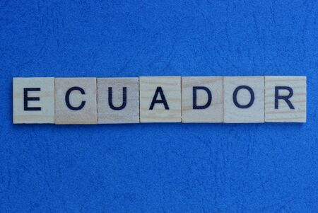gray word ecuador from small wooden letters on a blue table