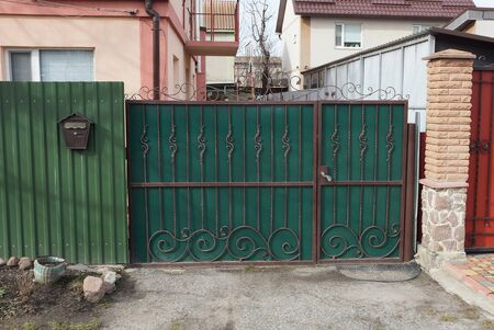 closed green private metal gate with an iron forged pattern and part of the fence on a rural street on a sunny day