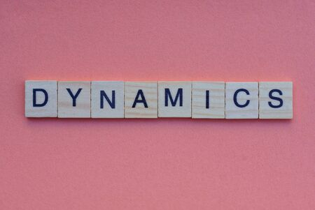 word dynamics from small gray wooden letters lies on a red background
