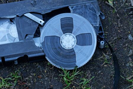 one old broken plastic video cassette is lying on the earth and grass
