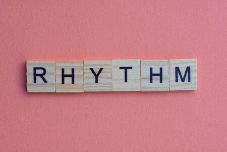 short small lettering rhythm in gray wooden letters with black font on a pink table