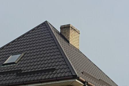 brick chimney on a tiled roof with a window on a background of gray sky Reklamní fotografie