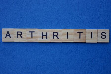 gray word arthritis from wooden small letters on a dark blue background
