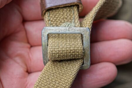 fingers hold a gray metal carbine on an old green harness made of fabric on a backpack Standard-Bild