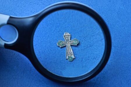 black magnifier enlarges a small old gray silver cross on a blue table