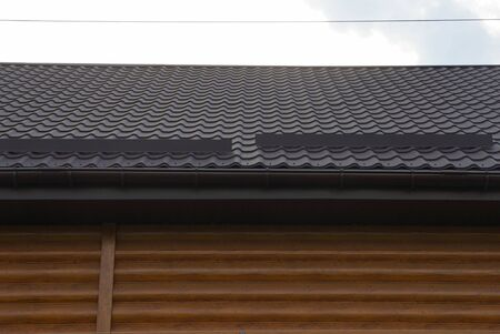part of a private house with a brown wooden wall and a tiled roof against the sky