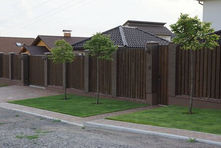 long private brown fence made of wooden boards and bricks with a closed front door on the street with green grass and decorative trees