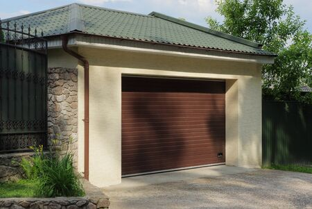 one concrete garage with closed brown gates under a green tiled roof outside on a sunny day
