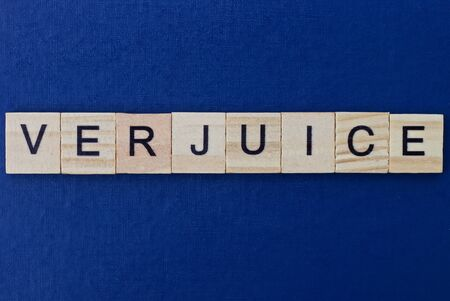 gray word verjuice in small square wooden letters with black font on a blue background