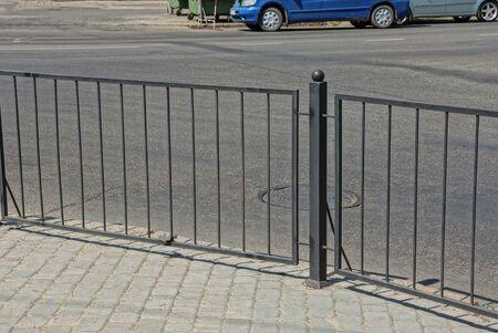 black metal decorative fence made of twigs on a gray sidewalk near an asphalt road