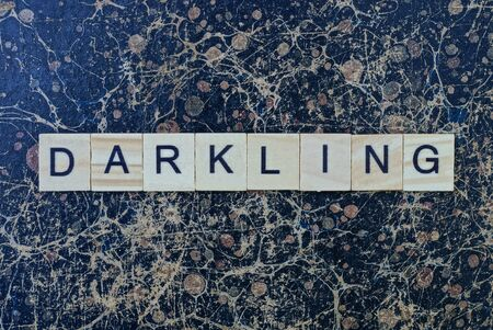 gray word darkling from wooden letters in black font on a brown shabby wall with a pattern