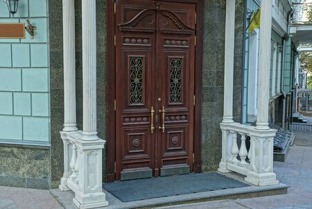 old brown wooden entrance door on a colored wall of a historic building on a city street