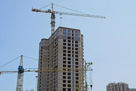two an iron tower crane and a large unfinished brown house against the sky