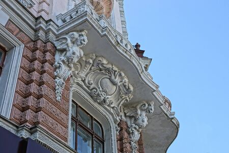 part of the brown concrete wall of a historic building with a window and a white balcony with sculptures