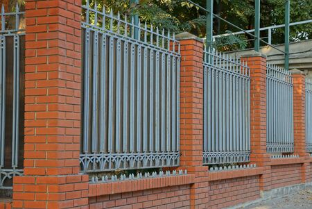 fence wall of red bricks and gray metal with sharp bars on the street Standard-Bild - 146383162
