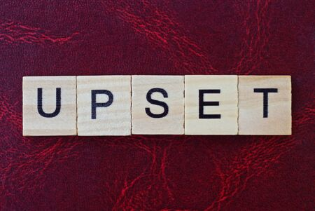 text the word upset from gray wooden small letters with black font on an red table Standard-Bild