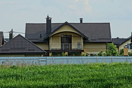 one large private house with a balcony under a brown tiled roof behind a gray metal fence in green grass