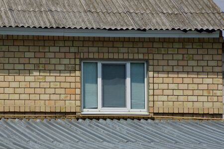 one white window on a brown brick wall of a house under a gray slate roof Standard-Bild