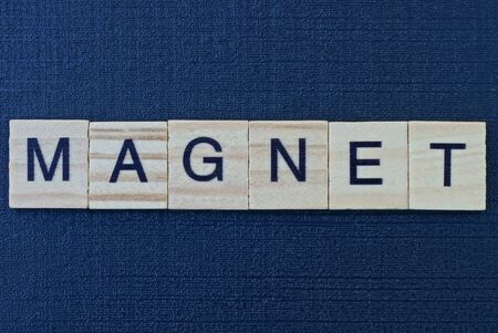 text the word magnet from gray wooden letters on a black table