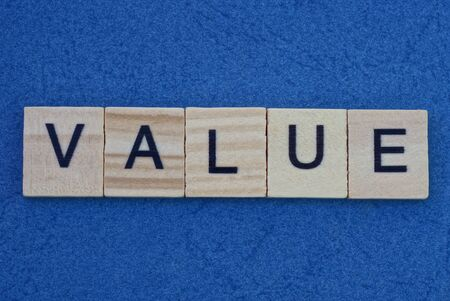 text the word value made from gray wooden letters lies on a blue background Standard-Bild