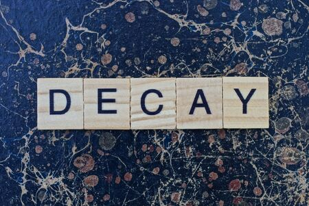 word decay from gray wooden small letters with black font