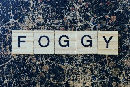text the word foggy from gray wooden small letters with black font