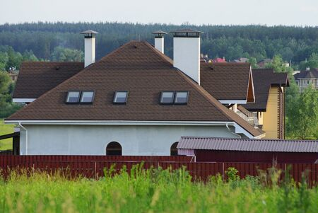 large white private house under a brown tiled roof with windows and chimneys behind a red fence in green grass