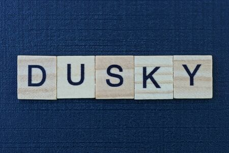 word dusky from gray wooden letters on a black background