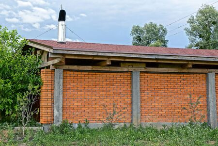 wall of a red brick house under a tiled roof in the green grass on the street