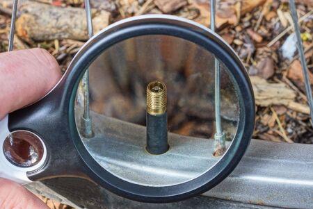 black magnifier in hand increases metal nipple on bicycle wheel