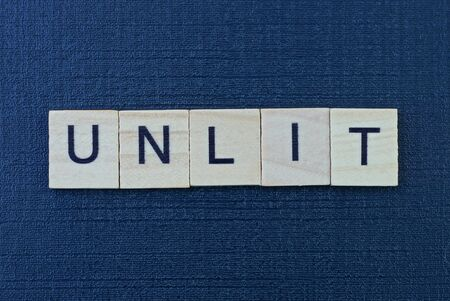word unlit from gray wooden letters on a black table Standard-Bild