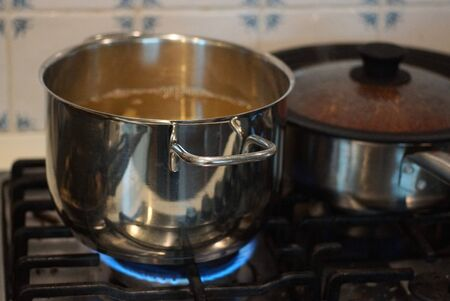 an open gray metal pan stands on the stove and is heated by a blue gas fire in the kitchen Standard-Bild