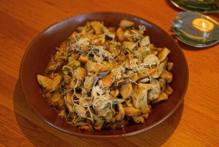 vegetarian dishes of fried mushrooms and grated cheese in a plate on a brown wooden table