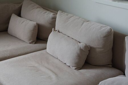 brown pillows on a large sofa against a gray wall in the room