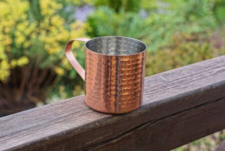 one empty red copper mug stands on a brown wooden board in the street