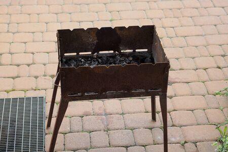 old brown iron barbecue box in rust stands on the sidewalk on the street