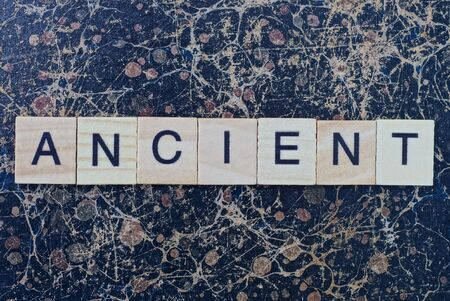 text the word ancient from gray wooden small letters with black font