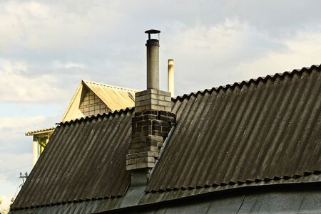 old dirty chimney on a gray slate roof of a rural house against a sky