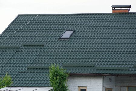 house roof with green tiles and one gray window against the sky Standard-Bild