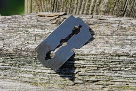 one black iron razor blade in a gray wooden fence board outdoors Standard-Bild