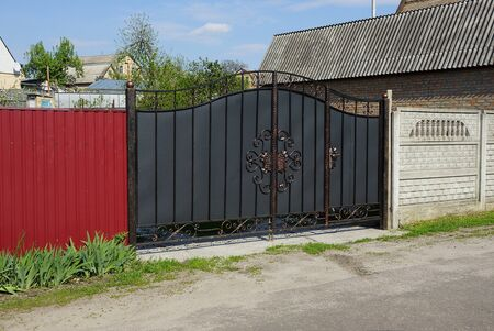 gray iron gate with black forged pattern and red fence on the street