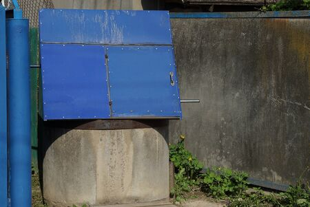 one blue closed metal well against a gray wall on a rural street