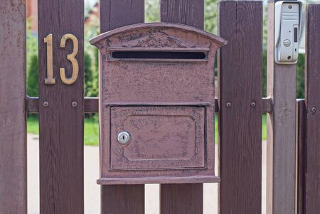 one brown metal mailbox on a wooden fence from boards with the number thirteen