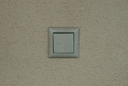 one white square plastic switch on a gray wall in the room