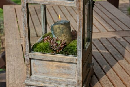 one big burning candle stands in green moss and plants in boxes of wood and glass stands on a wooden table in the street