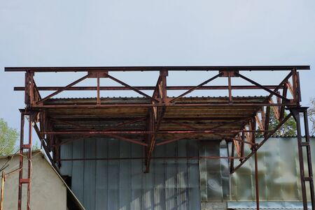 rusty brown iron ceiling overpass of an industrial old building against a blue sky 版權商用圖片