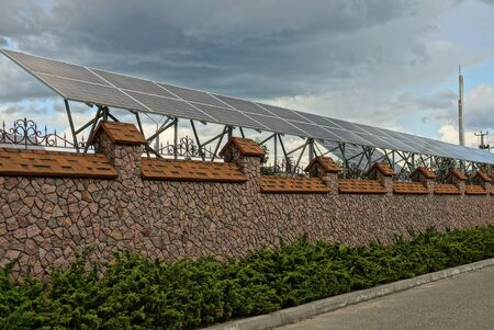 brown stone fence wall in green vegetation with solar panels on a background of gray clouds