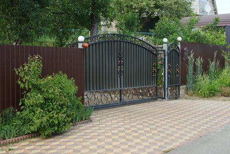 black iron gate and brown metal fence on the sidewalk on the street in green vegetation Standard-Bild