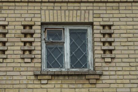 one white old wooden window with iron bars on the brown brick wall of the building Standard-Bild
