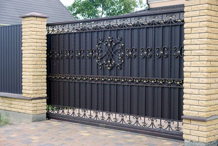 large closed brown wrought-iron gate and brick fence on the sidewalk